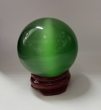 452.00 ct Green Cats Eye Sphere Gemstone With Rosewood Stand